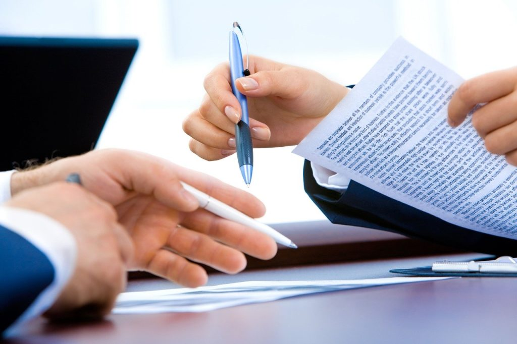 Picture of two people signing a contract